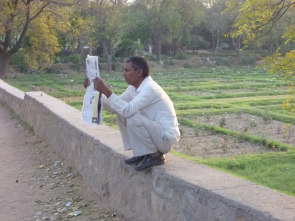How cool is this dude? Chilling out, squatting on a wall, reading his paper....