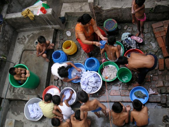 Saving both time and water by washing the children and the clothes at the same time!